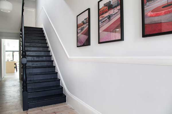 Restored Victorian pine floorboards with contrasting black staircase